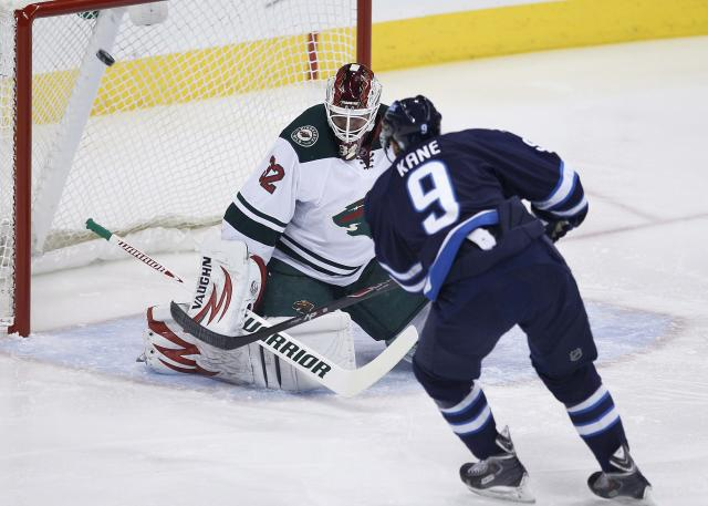Winnipeg Jets' Evander Kane (9) scores on Minnesota Wild's goaltender Niklas Backstrom (32) during first-period NHL hockey game action in Winnipeg, Manitoba, Friday, Dec. 27, 2013. (AP Photo/The Canadian Press, John Woods)