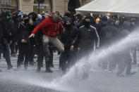 Water canon is used against demonstrators as they gather to protest against the COVID-19 restrictive measures at Old Town Square in Prague, Czech Republic, Sunday, Oct. 18, 2020. The Czech Republic has imposed a new series of restrictive measures in response to a record surge in coronavirus infections. Among the measures all sports indoor activities are banned and only up to 20 people are allowed to participate in outdoor sport activities also all bars, restaurants and clubs are closed while drinking of alcohol is banned at public places. (AP Photo/Petr David Josek)