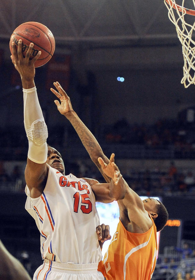 Florida forward Will Yeguete (15) shoots as Tennessee guard Antonio Barton (2) defends during the second half of an NCAA college basketball game Saturday, Jan. 25, 2014, in Gainesville, Fla. (AP Photo/Phil Sandlin)