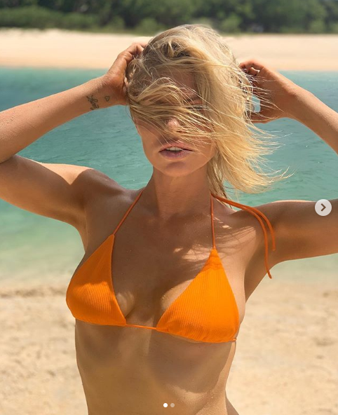 A photo of Sophie Monk wearing an orange bikini on the beach.