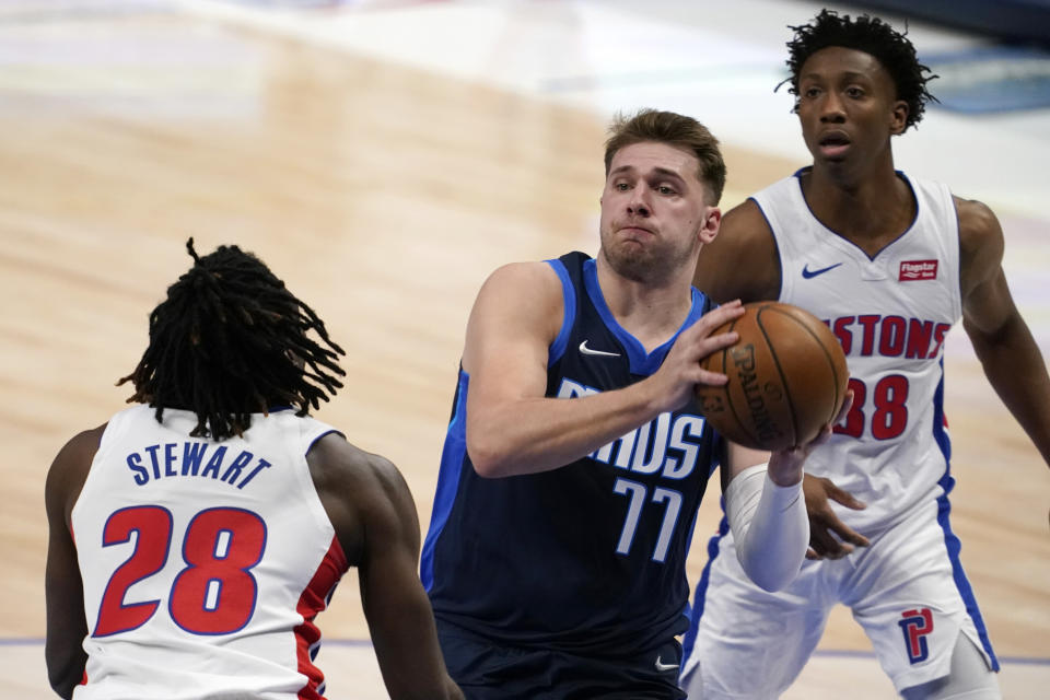 Detroit Pistons' Isaiah Stewart (28) and Saben Lee, rear, defend as Dallas Mavericks guard Luka Doncic (77) drives to the basket during the first half of an NBA basketball game in Dallas, Wednesday, April 21, 2021. (AP Photo/Tony Gutierrez)