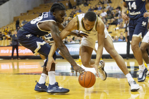 Missouri's Javon Pickett, right, and Charleston Southern's Dontrell Shuler, left, battle for a loose ball during the second half of an NCAA college basketball game Tuesday, Dec. 3, 2019, in Columbia, Mo. Charleston Southern won the game 68-60. (AP Photo/L.G. Patterson)