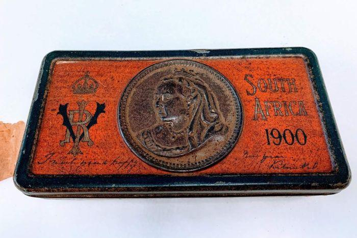 A rusted tin with an image of Queen Victoria.