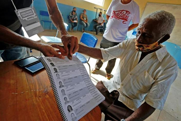 A man votes using his fingerprint to sign at a polling station in Igarape Miri, Para state, Brazil during the first round of municipal elections amid the new coronavirus pandemic on November 15, 2020