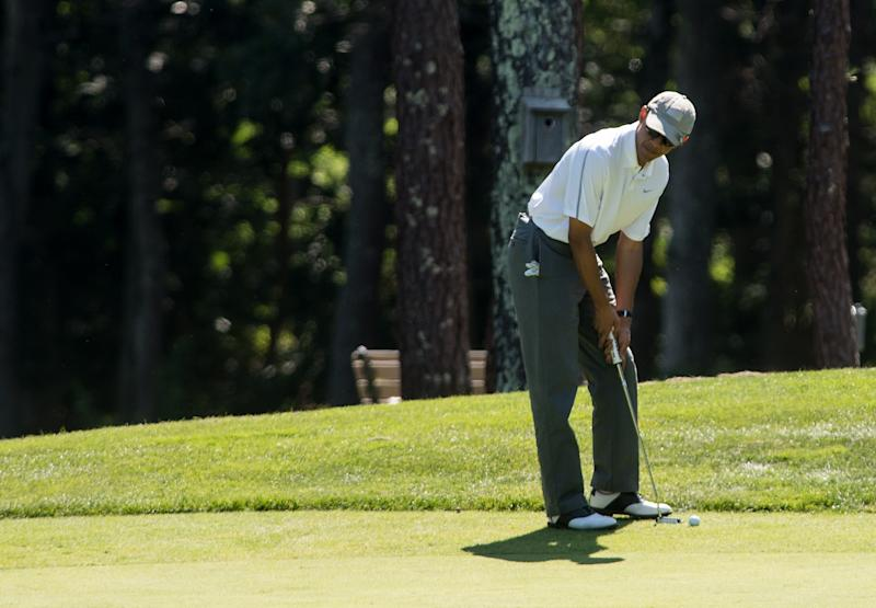 Barack Obama prepares to putt on the first green as he plays golf at the Farm Neck Golf Club at Martha's Vineyard, Massachusetts, on August 9, 2014