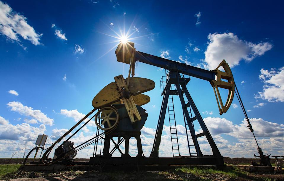 An oil pump with a bright sun and blue sky in the background.