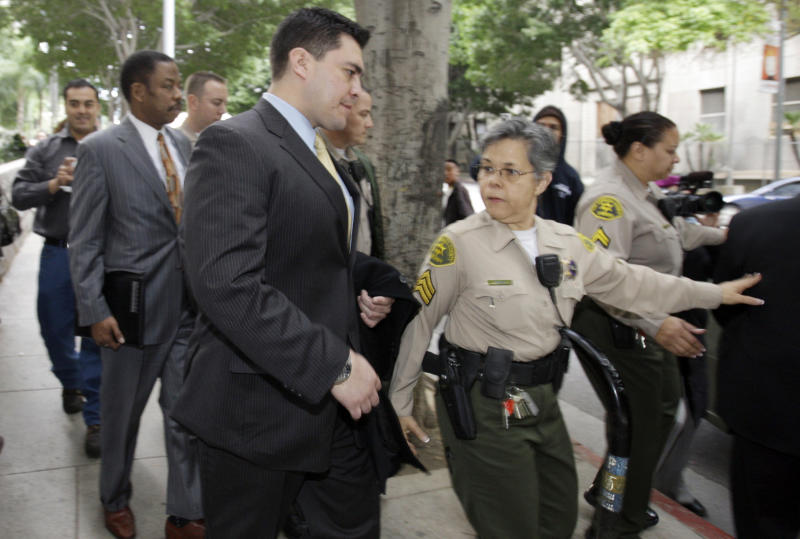 Security guard Alberto Alvarez, center, and his attorney Carl Douglas, left rear, they leave the preliminary hearing for Michael Jackson's doctor Conrad Murray, charged in the death of the singer, at Los Angeles Superior Court Wednesday, Jan. 5, 2011.  (AP Photo/Reed Saxon)