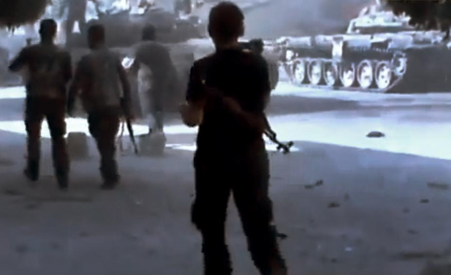 In this image made from amateur video released by the Ugarit News and accessed Monday, July 23, 2012, a Free Syrian Army soldier looks at a Syrian military that caught on fire during clashes with Syrian government troops in Aleppo, Syria. The Syrian regime acknowledged for the first time Monday that it possessed stockpiles of chemical and biological weapons and said it will only use them in case of a foreign attack and never internally against its own citizens. (AP Photo/Ugarit News via AP video) TV OUT, THE ASSOCIATED PRESS CANNOT INDEPENDENTLY VERIFY THE CONTENT, DATE, LOCATION OR AUTHENTICITY OF THIS MATERIAL