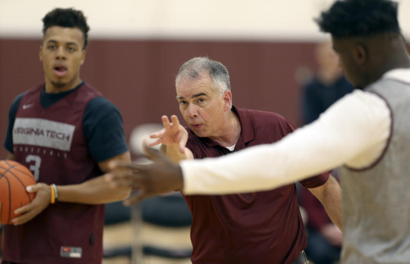In this Tuesday, Oct. 22, 2019 photo, Virginia Tech's first year head coach Mike Young, center, directs players Wabissa Bede (3) and Isaiah Wilkins (1) during NCAA college basketball practice in Blacksburg, Va. (Matt Gentry/The Roanoke Times via AP)