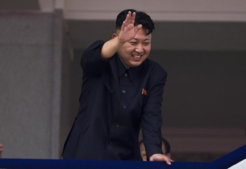 North Korean leader Kim Jong Un leans over a balcony and waves to Korean War veterans cheering below at the end of a mass military parade on Kim Il Sung Square in Pyongyang to mark the 60th anniversary of the Korean War armistice Saturday, July 27, 2013. (AP Photo/David Guttenfelder)
