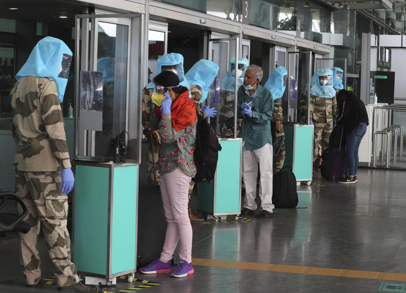 Indian security personnel wearing protective gear interact with passengers through glass before allowing them inside the departure terminal at Kempegowda International Airport in Bengaluru, India, Tuesday, June 2, 2020. More states opened up and crowds of commuters trickled onto the roads in many of India's cities on Monday as a three-phase plan to lift the nationwide coronavirus lockdown began despite an upward trend in new infections. (AP Photo/Aijaz Rahi)