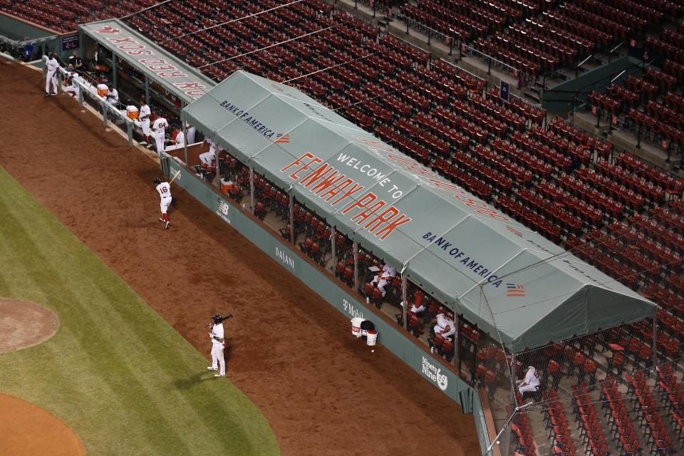 Boston Red Sox players spread out in an expanded dugout during the fifth inning of an opening day baseball game against the Baltimore Orioles at Fenway Park, Friday, July 24, 2020, in Boston. (AP Photo/Michael Dwyer)