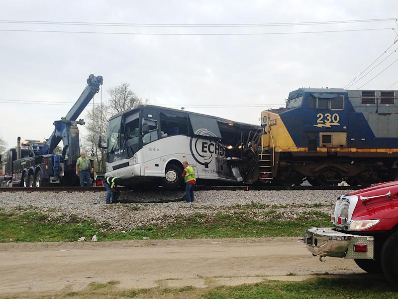 Men prepare to move a charter bus after a freight train crashed into the bus in Biloxi, Mississippi: AP