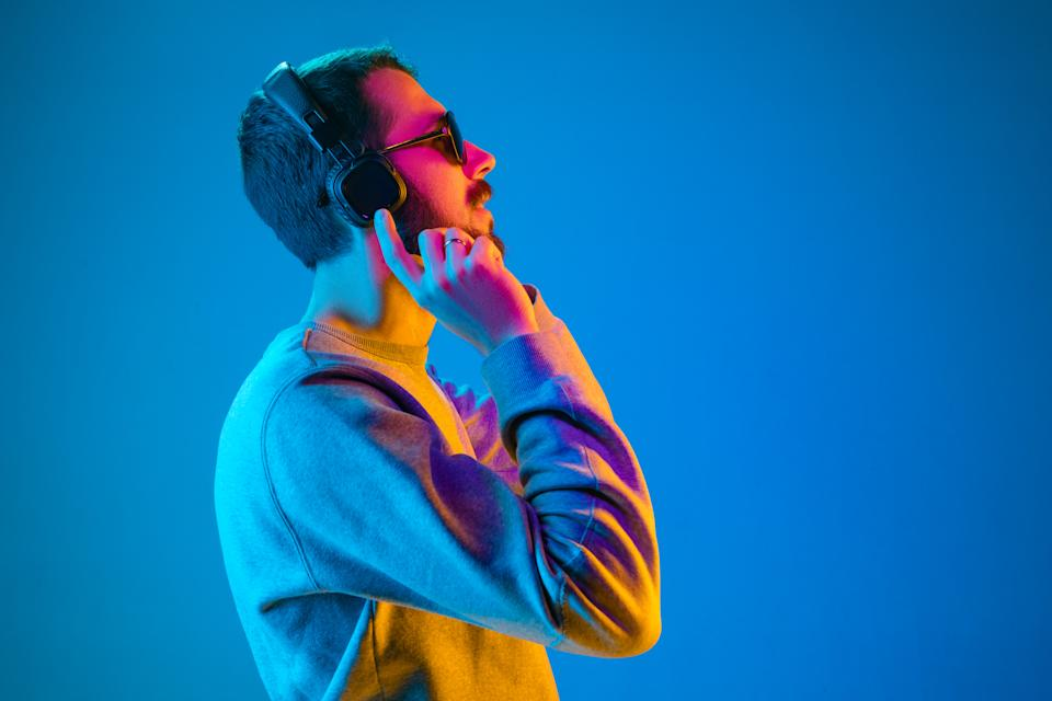 Enjoying his favorite music. Happy young stylish man in sunglasses with headphones listening and smiling while standing against blue neon background