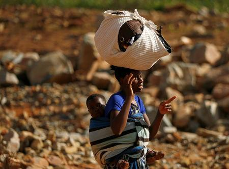 A survivor of Cyclone Idai carries her baby as she moves to higher ground at Ngangu suburb in Chimanimani, Zimbabwe, March 22, 2019. REUTERS/Philimon Bulawayo