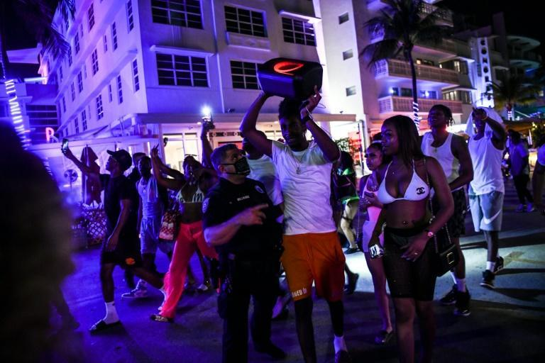 Miami Beach Police detain a man as he plays loud music on a wireless speaker on Ocean Drive on March 17, 2021