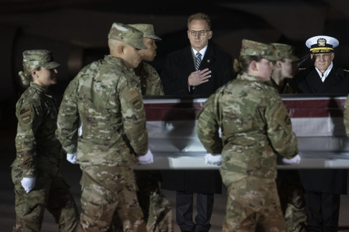 Acting Navy Secretary Thomas Modly, center, and Adm. Michael Gilday, chief of naval operations, look on as an Air Force team moves a transfer case containing the remains of Navy Ensign Joshua Kaleb Watson. Watson was killed in the mass shooting in Pensacola, Fla., on Dec. 6. (Photo: Cliff Owen/AP)