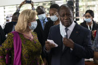 Ivory Coast President Alassane Ouattara removes his mask as he stands next to his wife Dominique Ouattara, left, after voting in a polling station during presidential elections in Abidjan, Ivory Coast, Saturday, Oct. 31, 2020. Tens of thousands of security forces deployed across Ivory Coast on Saturday as the leading opposition parties boycotted the election, calling President Ouattara's bid for a third term illegal. (AP Photo/Leo Correa)