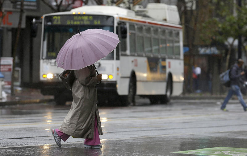 A woman carries an umbrella as she crosses Market Street in San Francisco, Saturday, Feb. 8, 2014. Californians accustomed to complaining about the slightest change in the weather welcomed a robust weekend storm that soaked the northern half of the drought-stricken state Saturday even as rain and snow brought the threat of avalanches, flooding and rock slides. (AP Photo/Jeff Chiu)