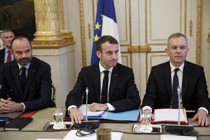 French President Emmanuel Macron, center, French Prime Minister Edouard Philipppe, left, and Environment Minister Francois de Rugy meet with representatives of trade unions, employers' organizations and local elected officials at the Elysee Palace in Paris, Monday, Dec.10 2018. Macron is preparing to speak to the nation Monday at last, after increasingly violent and radicalized protests against his leadership and a long silence that aggravated the anger. (Yoan Valat, Pool via AP)