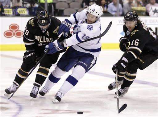 Tampa Bay Lightning center Dominic Moore (19) fights Dallas Stars center Steve Ott (29) and right wing Adam Burish (16) for control of a puck in the second period of an NHL hockey game, Friday, Jan. 20, 2012, in Dallas. (AP Photo/Tony Gutierrez)