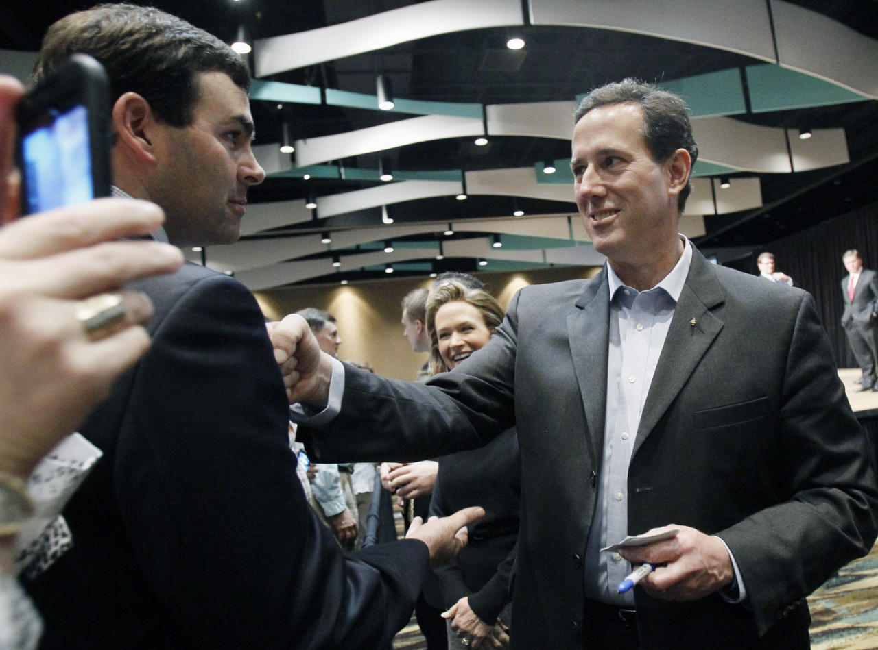 """Republican presidential candidate, former Pennsylvania Sen. Rick Santorum, right, jokingly """"punches"""" Mississippi State Sen. Michael Watson, R-Pascagoula, as he asks for continued support following a speech at the Gulf Coast Energy Summit in Biloxi, Miss., March 12, 2012. (AP Photo/Rogelio V. Solis)"""