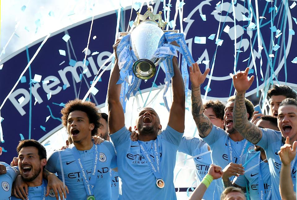 """Soccer Football - Premier League - Brighton & Hove Albion v Manchester City - The American Express Community Stadium, Brighton, Britain - May 12, 2019  Manchester City's Vincent Kompany lifts the trophy as they celebrate winning the Premier League               REUTERS/Toby Melville  EDITORIAL USE ONLY. No use with unauthorized audio, video, data, fixture lists, club/league logos or """"live"""" services. Online in-match use limited to 75 images, no video emulation. No use in betting, games or single club/league/player publications.  Please contact your account representative for further details."""