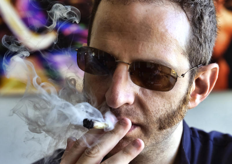 In this Saturday, Aug. 25, 2018 photo, Judd Weiss takes a puff of a pre-rolled marijuana cigarette at his house in the Bel Air section of Los Angeles. Weiss, CEO and founder of cannabis company Lit.Club, believes the industry needs to do still more. He suggests marketing products in a way that makes them look more than just respectable, but as the herbal equivalent of a fine bourbon or scotch. (AP Photo/Richard Vogel)