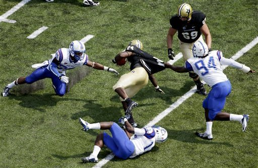 Vanderbilt wide receiver Wesley Tate (24) is brought down by Presbyterian defenders L. J. Perry (35), Mark Williams (13), and Keyadd Miller (94) in the first quarter of an NCAA college football game, Saturday, Sept. 15, 2012, in Nashville, Tenn. Coming in to help Tate is Vanderbilt guard Josh Jelesky (69). (AP Photo/Mark Humphrey)