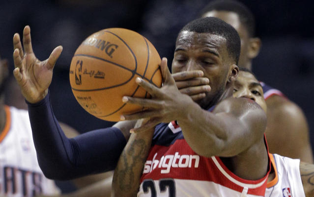 Washington Wizards' Shelvin Mack, front, is fouled by Charlotte Bobcats' Tyrus Thomas, back, during the second half of an NBA basketball game in Charlotte, N.C., Monday, April 9, 2012. Washington won 113-85. (AP Photo/Chuck Burton)