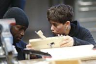 An instructor (R) speaks with a refugee during a workshop organized by the Arrivo Berlin initiative to offer new professional skills, in Berlin, Germany, December 17, 2015. REUTERS/Hannibal Hanschke