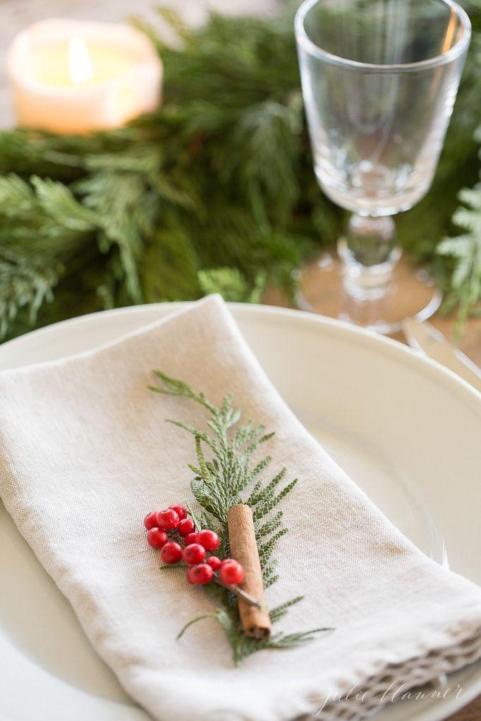 "<p>A sprig of fresh greenery, a few berries, and a cinnamon stick are all you need to dress your place setting at a small informal event. You could attach a place card, too, for an inexpensive but classic seasonal accent. </p><p><strong>See more at <a href=""https://julieblanner.com/garland-centerpiece/"" rel=""nofollow noopener"" target=""_blank"" data-ylk=""slk:Julie Blanner."" class=""link rapid-noclick-resp"">Julie Blanner.</a></strong></p>"