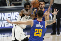Brooklyn Nets guard Kyrie Irving is defended by Denver Nuggets guards Austin Rivers, front, and Facundo Campazzo during the second half of an NBA basketball game Saturday, May 8, 2021, in Denver. (AP Photo/David Zalubowski)