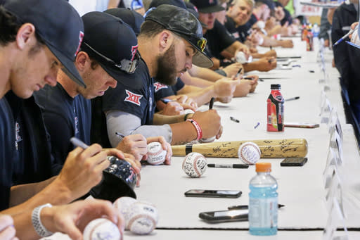 Texas Tech NCAA college baseball players sign autographs for fans following practice at TD Ameritrade Park in Omaha, Neb., Friday, June 14, 2019. Texas Tech plays Michigan on Saturday in the College World Series. (AP Photo/Nati Harnik)