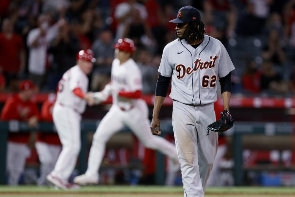 Detroit Tigers starting pitcher Jose Urena, right, looks over as Los Angeles Angels' Shohei Ohtani, center, celebrates his two-run home run with third base coach Brian Butterfield during the fifth inning of a baseball game in Anaheim, Calif., Friday, June 18, 2021. (AP Photo/Alex Gallardo)