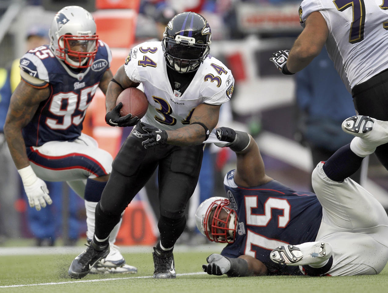 Baltimore Ravens running back Ricky Williams (34) runs between New England Patriots defensive end Mark Anderson (95) defensive tackle Vince Wilfork (75) during the first half of the AFC Championship NFL football game Sunday, Jan. 22, 2012, in Foxborough, Mass. (AP Photo/Winslow Townson)