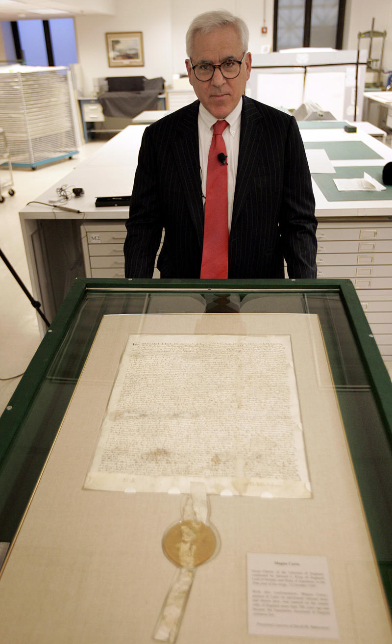 FILE - In this March 3, 2008 file photo, David Rubenstein poses with a 1297 Magna Carta document,  at the National Archives in Washington. Weeks of intensive conservation treatment of a rare version of the Magna Carta has revealed previously illegible writing in the text of the 1297 document. A gift from philanthropist Rubenstein will fund a major new exhibit for the document, which he has loaned to the National Archives.  (AP Photos/Susan Walsh, File)