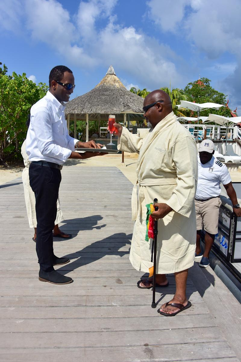 Herman Gordon accepts a drink from a waiter at Sandals Resorts in Jamaica after students at the University of Bristol crowdfunded the money for their flights