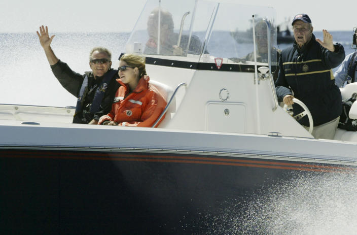 <p>Former President George H.W. Bush (right) and his son President George W. Bush wave as they fish off Boon Island near Kennebunkport, Maine, on Aug. 8, 2004. With them is the president's daughter Jenna. (Photo: Stephan Savoia/AP) </p>