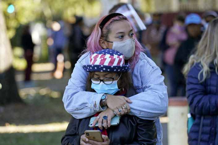 Erin Doherty hugs her mother Susanna Dew, 61, who is voting for the first time, as they wait in line at a polling place on Election Day in the Mid City section of New Orleans on Nov. 3, 2020. (Gerald Herbert/AP)
