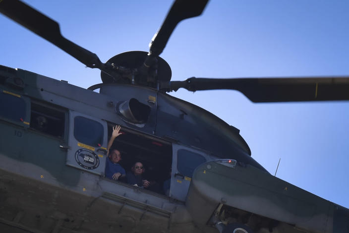 Brazil's President Jair Bolsonaro waves to supporters from a military helicopter overflying the presidential palace in Brasilia, Brazil, Sunday, May 31, 2020. Bolsonaro mounted a horse from police that were guarding supporters of his government gathered outside the Planalto Palace. (AP Photo/Andre Borges)