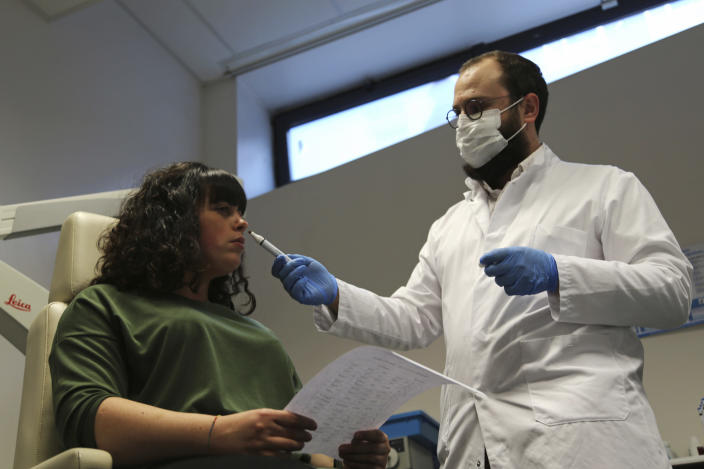 Dr. Clair Vandersteen, right, wafts a tube of odors under the nose of a patient, Gabriella Forgione, during tests in a hospital in Nice, southern France, Monday, Feb. 8, 2021, to help determine why she has been unable to smell or taste since she contracted COVID-19 in November 2020. A year into the coronavirus pandemic, doctors and researchers are still striving to better understand and treat the accompanying epidemic of COVID-19-related anosmia — loss of smell — draining much of the joy of life from an increasing number of sensorially frustrated longer-term sufferers like Forgione. (AP Photo/John Leicester)