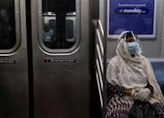 A woman wearing a face mask and shield sits in a New York subway train during rush hour amid the coronavirus pandemic on July 16, 2020; as many people turn away from mass transit, bicycle use has exploded