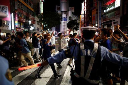 Police officers try to control soccer fans and pedestrians on a diagonal crosswalk after World Cup Group H soccer match Japan vs Senegal, at Shibuya district in Tokyo, Japan June 25, 2018. REUTERS/Issei Kato