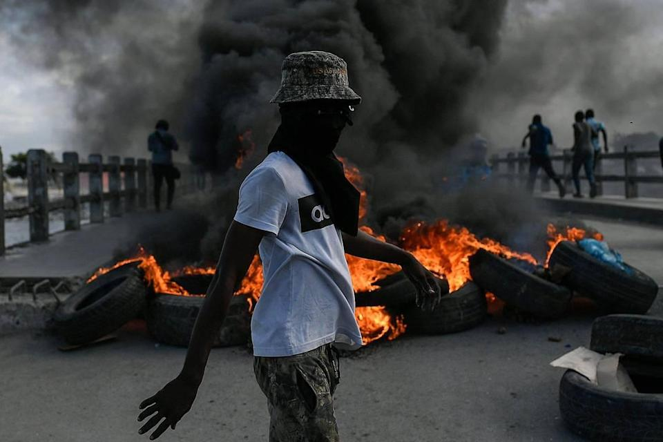 A protester demanding justice for the assassinated President Jovenel Moïse stands near a burning barricade in Cap-Haitien, Haiti, Thursday, July 22, 2021. Demonstrations after a memorial service for Moïse turned violent on Thursday afternoon with protesters shooting into the air, throwing rocks and overturning heavy concrete barricades next to the seashore as businesses closed and people took cover.