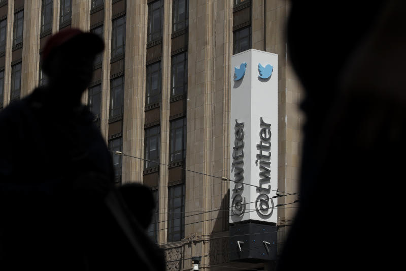 FILE - This July 9, 2019, file photo shows pedestrians walking across the street from the Twitter office building in San Francisco. The Saudi government recruited two Twitter employees to get personal account information of their critics, prosecutors said Wednesday, Nov. 6, 2019. (AP Photo/Jeff Chiu, File)