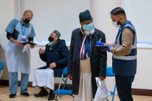 People attend a temporary coronavirus vaccination centre at the East London Mosque, in Whitechapel