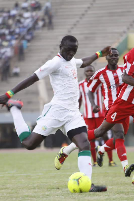 Senegal national team player Papiss Cisse (L) kicks the ball in front of Kenya national team players on January 15, 2012 during a friendly match ahead of the 2012 Africa Cup of Nations at the Leopold Sedar Senghor stadium in Dakar. AFP PHOTO / MAMADOU TOURE BEHAN