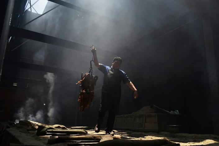 A Uighur man carries chicken from an underground oven at a restaurant in Hotan in China's northwest Xinjiang region in May 2019 (AFP Photo/Greg Baker)