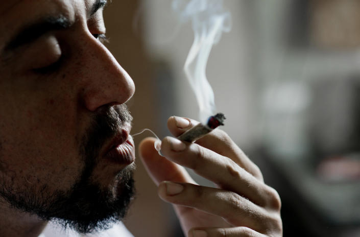 Marcelo Vazquez, a marijuana grower, smokes a marijuana cigarette, on the outskirts of Montevideo, Uruguay, Monday, Dec. 9, 2013. The Uruguayan Senate is expected to approve a law to legalize the production, distribution and sale of marijuana Tuesday. If approved, Uruguay would be the first country to regulate the marijuana market from production to retail. (AP Photo/Matilde Campodonico)